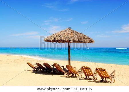 Umbrella and wooden chairs on tropical Caribbean beach at Maguana, Cuba