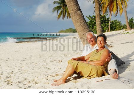 Happy senior couple sitting on the beach embracing each other, enjoying retirement on tropical destination: Maria la Gorda on caribbean island Cuba
