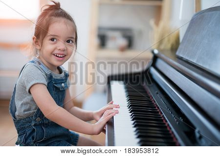Little girl play piano and sing a song in living room music kid baby child concept