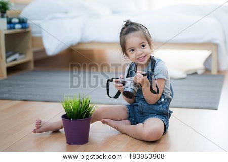 Girl smile and view a picture in camera and sit in the room nature photographercamera and relax concept