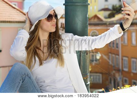 Young pretty girl makes selfie photo on a cell phone in an urban environment on a sunny summer day