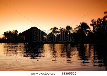 Romantic sunrise in Zapata swamp area with silhouette of bamboo cottages and palm trees on caribbean island Cuba