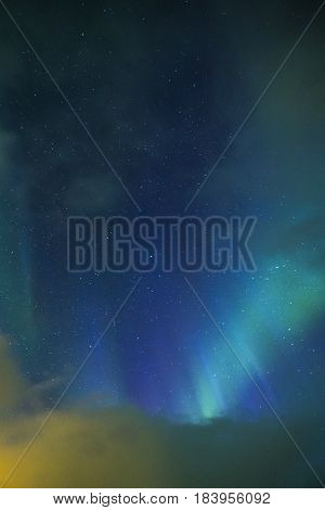 Aurora Borealis Known as Northern Lights Playing with Vivid Colors Over Lofoten Islands in Norway. Vertical Image Composition