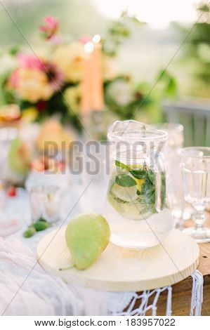 picnic, food, summer, holiday concept - glass jug full of lemonade on festive table, pear, flagon with water, slices of lemon, lime, mint, background of bouquet, candles, glasses