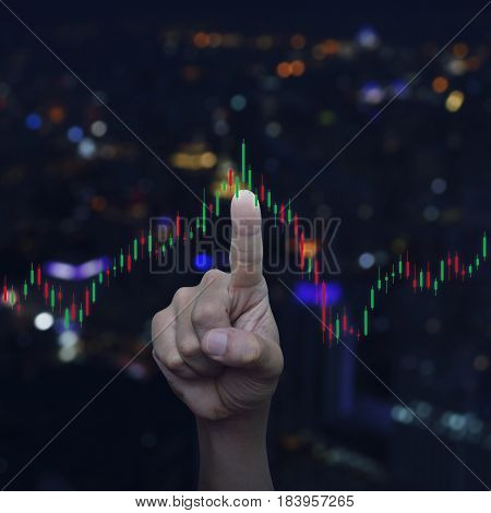 Hand pressing to trading graph of stock market over blur colourful night light city tower Business investment concept