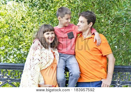 Happy family pregnant mother father and son looking to each others
