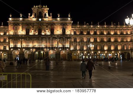 SALAMANCA, SPAIN - MAR 29, 2017: Pedestrians take the evening air in the Plaza Mayor at night.
