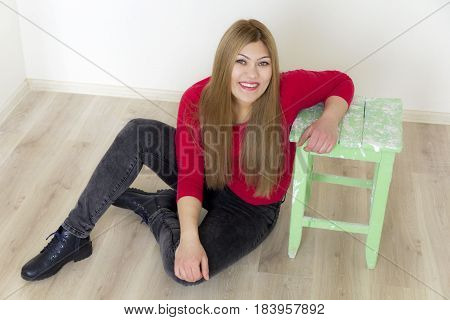 Girl with long brown healthy hair sitting on floor in red