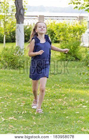 Cute running European girl with disheveled hair in green park