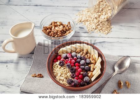 Oatmeal in brown clay bowl with frozen berries as blackcurrants, redcurrants, blackberries, bananas and walnuts ready to eat, jug with milk and spoon on the light wooden table