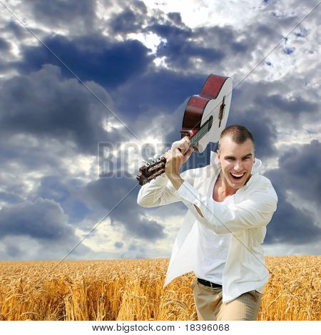 Enthusiastic man smashing with his guitar outdoors in the field with cloudy sky square background