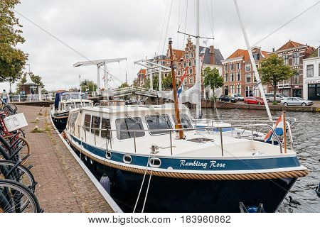 Haarlem Netherlands - August 3 2016: Picturesque landscape with beautiful traditional houses bridge and vessel in canal of Haarlem