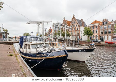 Haarlem Netherlands - August 3 2016: Picturesque landscape with beautiful traditional houses bridge and vessels in canal of Haarlem