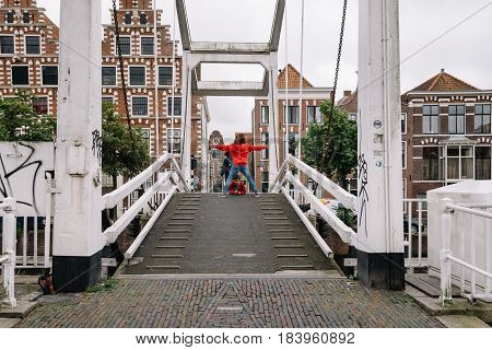 Haarlem Netherlands - August 3 2016: Picturesque landscape with beautiful traditional houses and prople crossing the bridge over canal of Haarlem