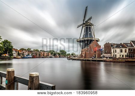 Haarlem Netherlands - August 3 2016: Picturesque and beautiful long exposure landscape with the windmill the river and traditional houses in Haarlem Netherlands
