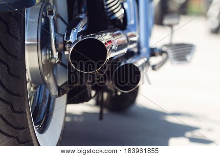 rear view of classical motorcycle pair of exhaust chrome pipes selective focus