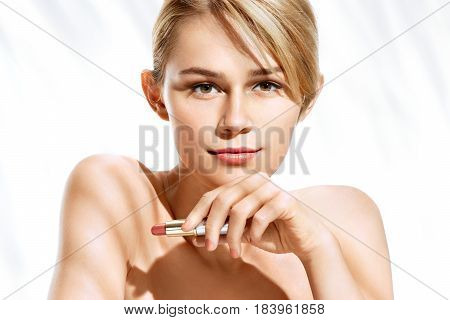 Attractive young girl with lipstick on white background. Photo of blonde girl with perfect make up. Beauty concept