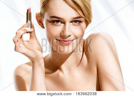 Gorgeous blonde woman with lipstick on white background. Youth and skin care concept