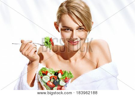 Smiling beautiful woman with healthy vegetable salad. Photo of blonde woman in bathrobe isolated on white background. Diet. Healthy lifestyle