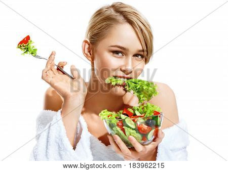 Sexy young woman eating healthy vegetable salad. Photo of attractive lady of the european appearance isolated on white background. Healthy lifestyle