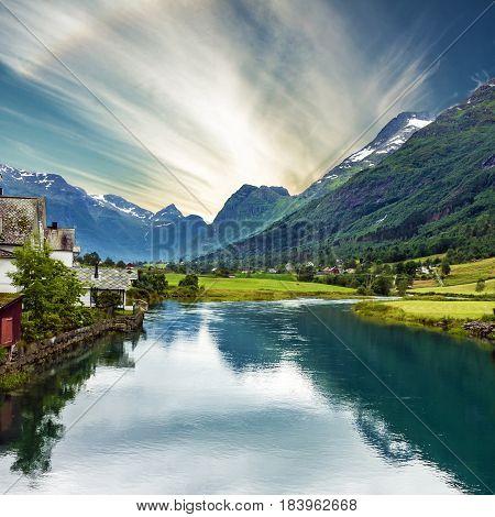 rural lake landscape, Norway, Olden, green hills seaside. fjord in summer.