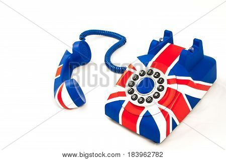 Photo Union Jack telephone with pattern of British flag telephone with the receiver off the hook laying near the phone isolated on the white background.