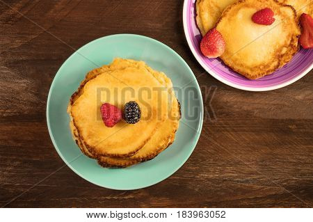 A photo of homemade pancakes with fresh strawberry and raspberry, shot from above on a dark brown wooden texture with copy space