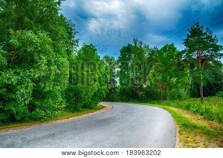 Summer landscape of summer suburban forest in cloudy weather - deserted suburban road in the summer forest under dramatic cloudy sky. Summer background. Summer landscape view with summer forest nature. Soft filter applied.