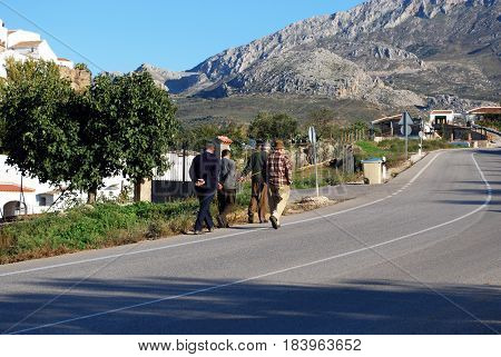 EL BURGO, SPAIN - OCTOBER 29, 2008 - Four elderly Spanish men walking along the road on the edge of the village El Burgo Malaga Province Andalusia Spain Western Europe, October 29, 2008.