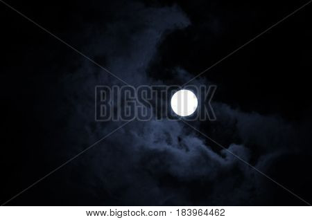 Night mysterious landscape in cold tones - full moon in the night sky and dramatic night clouds. Night sky background. Sinister night landscape with full night moon between the night clouds