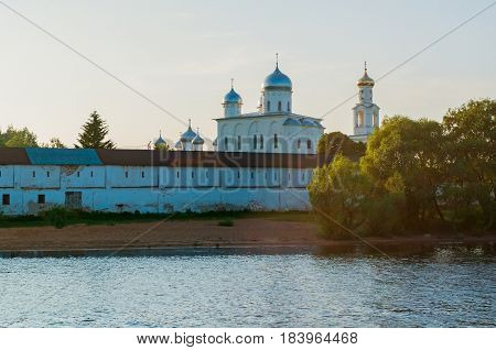 Veliky Novgorod Russia.Sunset architecture landscape - view of bell tower and cathedrals in Yuriev male monastery on the bank of the Volkhov river in Veliky Novgorod Russia. Sunset summer architecture view in the backlight