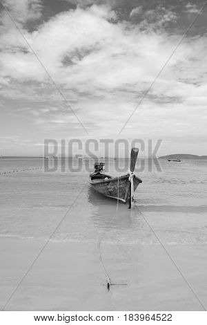 Traditional long tail boat on Railay Beach with blue sea and blue sky background, Krabi, Thailand. (Black and White filter effect)