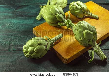 A low-key photo of green artichokes on dark rustic textures with a place for text