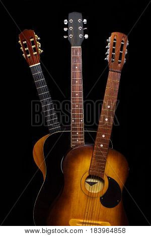 Three acoustic guitars on black background. Isolated.