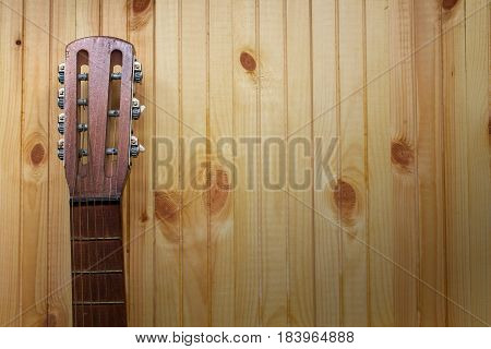 Acoustic guitar headstock against a wooden background with copy space