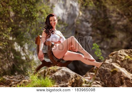 Busty young woman sitting in underwear in the mountains on a Spanish chair.
