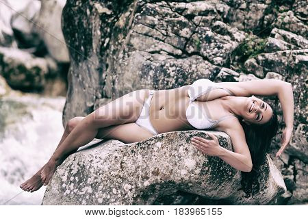 Busty young woman lies in white lingerie on a rock at a rushing mountain stream.