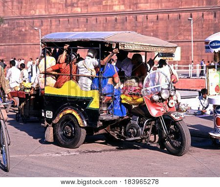 DELHI, INDIA - NOVEMBER 20, 1993 - View of the Red Fort with local people on a tuk-tuk in the foreground Delhi Delhi Union Territory India, November 20, 1993.