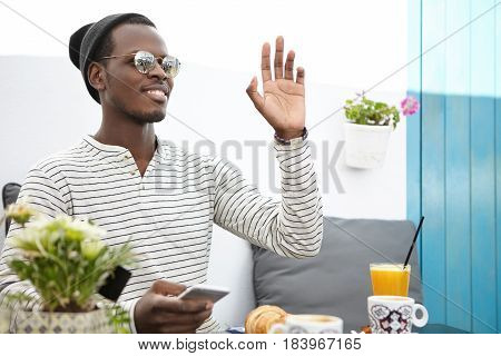 Happy Dark-skinned Male Wearing Striped Long Sleeved T-shirt, Hat And Sunglasses Messaging Online Us