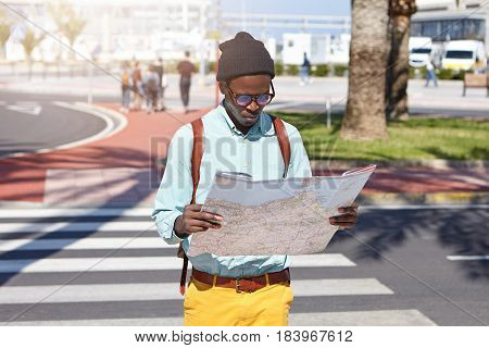 Outdoor Urban Shot Of Serious Dark-skinned European Traveler In Stylish Clothing Standing In The Mid
