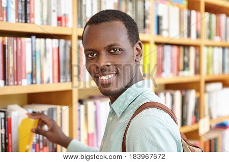 Indoor Portrait Of Handsome African Man Picking Book From Shelve In Bookshop As Present On His Frien