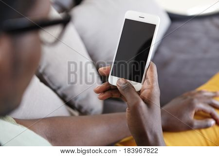 Cropped Indoor Image Of Unrecognizable Dark-skinned Man Relaxing On Couch In Living Room, Using Home