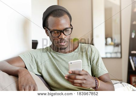 Indoor Portrait Of Fashionable Young Afro American Man Having Rest At Home, Sitting On Sofa With Tou