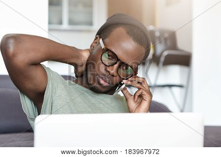 Dark-skinned Young Male Freelancer Talking On Mobile While Sitting In Front Of Open Laptop Computer
