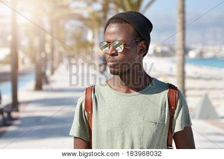 Confident Serious African American 20-year Old Man With Backpack Walking Along Street On Summer Sunn