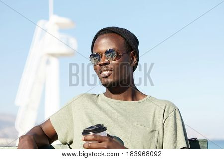 Cheerful Handsome Young Dark-skinned Man Enjoying Nice Summer Day At Seaside, Drinking Takeaway Coff