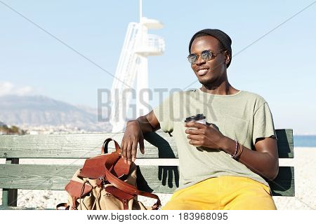 Handsome Young Black European Male Traveler Dressed In Trendy Clothing Having A Few Minutes Rest On