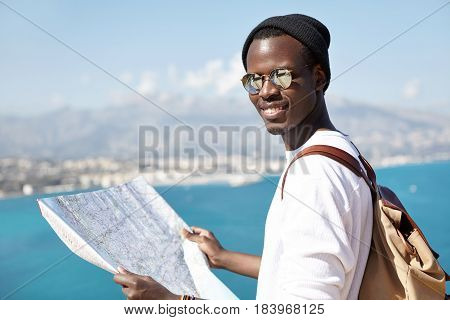 Outdoor Shot Of Atrractive Trendy Looking Dark-skinned Tourist Studying Paper Map In His Hands, Wear