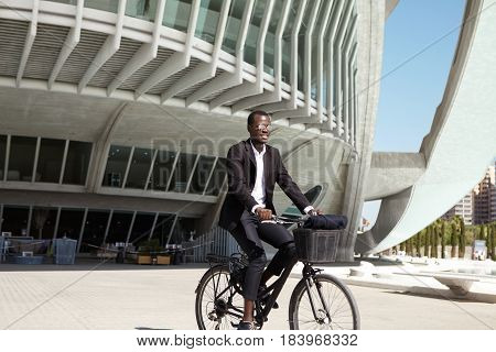 Ecologically Conscious Young Black European Businessman Wearing Black Suit And Sunglasses Cycling To