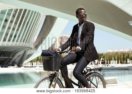 Successful Happy African American Manager In Black Suit Commuting To Office On Bicycle. Dark-skinned